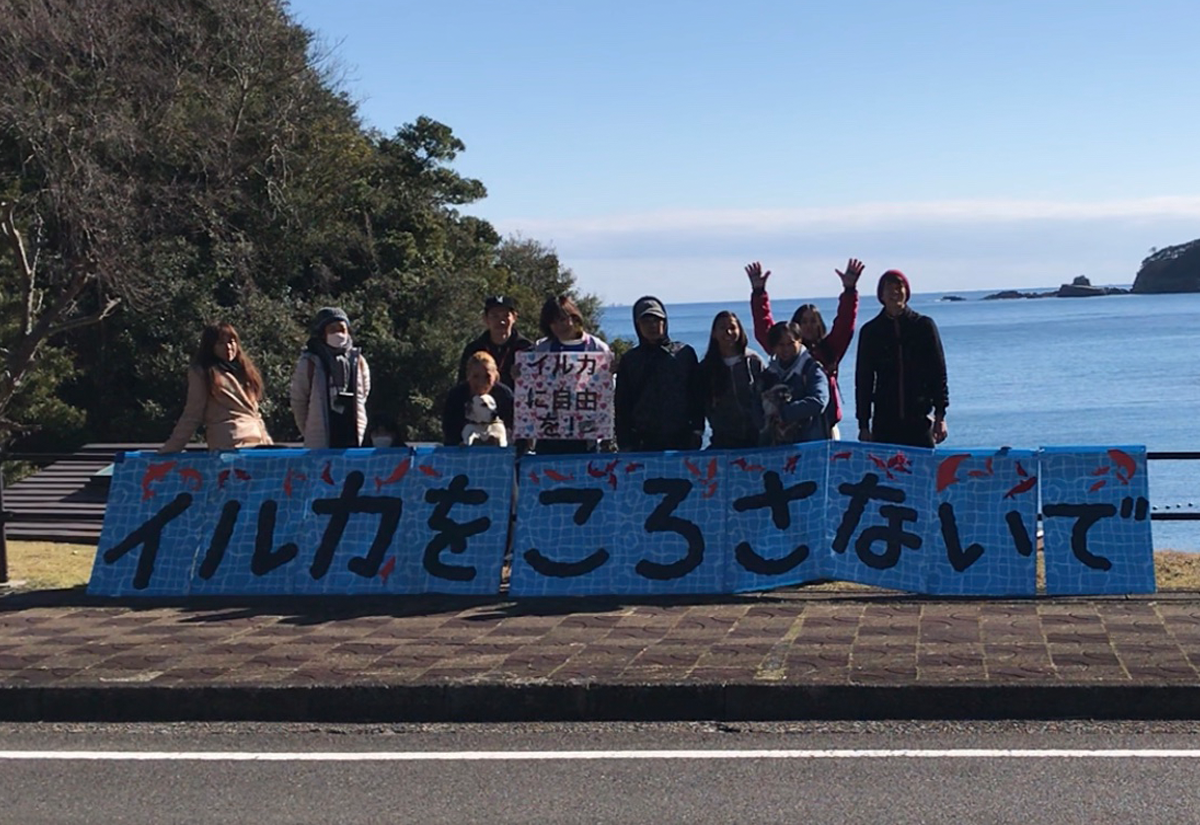 """Japanese activists at the Cove with a sign that says """"Don't kill dolphins"""""""